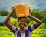 Cookstoves Malawi Stove production group member poses in tea field with stove